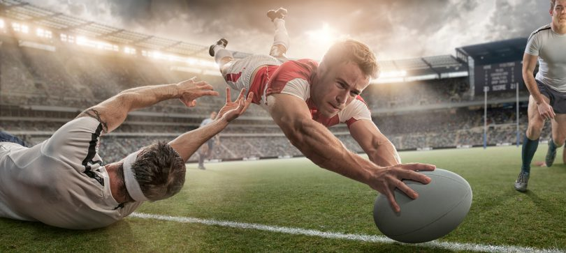 Mid action image of a professional rugby player diving in mid air with rugby ball held out about to place ball over line about to score a try, whilst being tackled by opposition player. The action occurs in a generic outdoor floodlit rugby stadium full of spectators under a dramatic sunset sky.